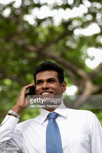 Portrait of Indian man talking on phone and smiling outdoors : Stock Photo