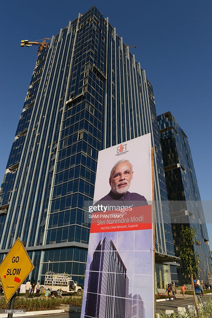 A portrait of India's Gujarat state Chief Minister Narendra Modi is seen in front of the GIFT City Tower 1 during the eve of its inauguration in the outskirts of Gandhinagar, some 30 kms. from Ahmedabad, on January 9, 2013. The tower, the state's tallest building located in the Gujarat International Finance Tec-City (GIFT), will be officiated by Modi on January 10. AFP PHOTO / Sam PANTHAKY