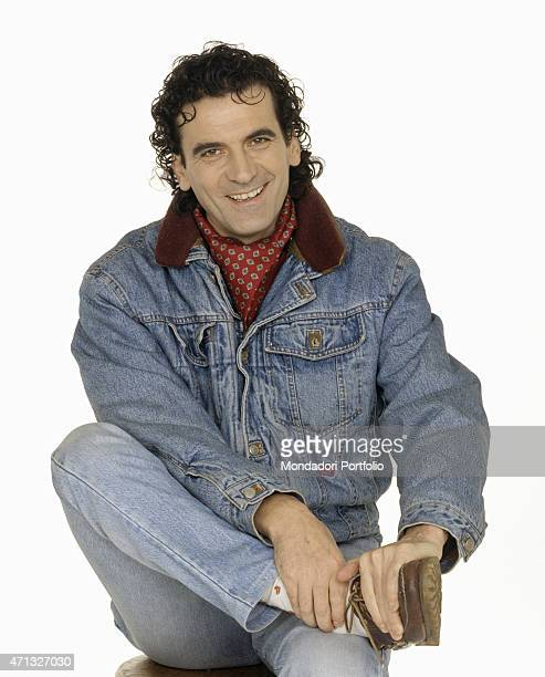 Portrait of Italian actor and director Massimo Troisi smiling on a stool 1991