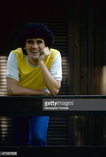 Portrait of Italian actor and director Massimo Troisi smiling wearing a yellow vest 1981