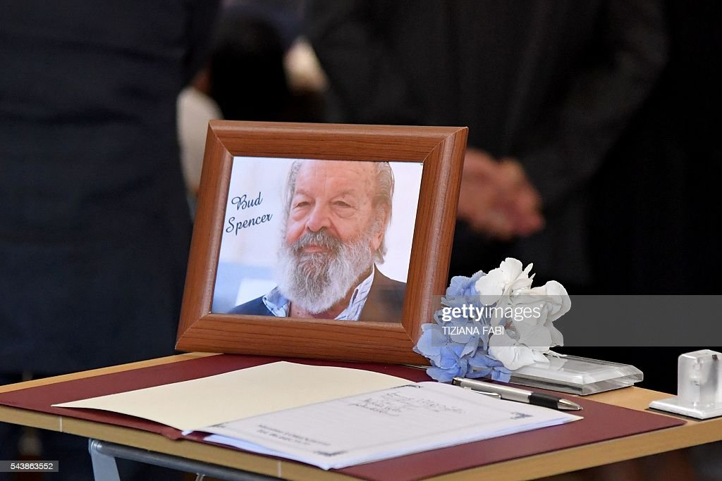 A portrait of Italian actor Bud Spencer, born Carlo Pedersoli, is seen near a book of condolences in the 'church of the artists', Santa Maria in Montesanto, on June 30, 2016 during the funeral of the actor at Piazza del Popolo in Rome. Bud Spencer who starred in a string of spaghetti westerns, died on June 27 in Rome aged 86. Spencer, born in Italy in 1929, played in 16 films alongside Terence Hill, whose real name was Mario Girotti. He was also an Italian swimming champion and in 1950, he became the first Italian to swim the 100-metre freestyle in under a minute. / AFP / TIZIANA