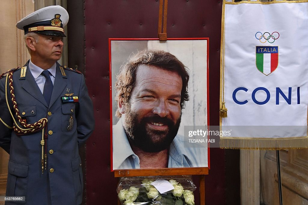 A portrait of Italian actor Bud Spencer, born Carlo Pedersoli, is seen next to a flag of the Italian Olympic Commitee at the church of the artists, Santa Maria in Montesanto, on June 30, 2016 before the funeral the actor at Piazza del Popolo in Rome. Bud Spencer who starred in a string of spaghetti westerns, died on June 27 in Rome aged 86. Spencer, born in Italy in 1929, played in 16 films alongside Terence Hill, whose real name was Mario Girotti. He was also an Italian swimming champion and in 1950, he became the first Italian to swim the 100-metre freestyle in under a minute. / AFP / TIZIANA