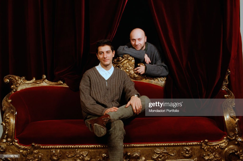 Portrait of Italian fashion designers Domenico Dolce and Stefano Gabbana sitting on a red velvet sofa. 1980s