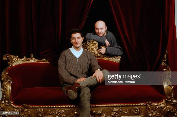 Portrait of Italian fashion designers Domenico Dolce and Stefano Gabbana sitting on a red velvet sofa 1980s