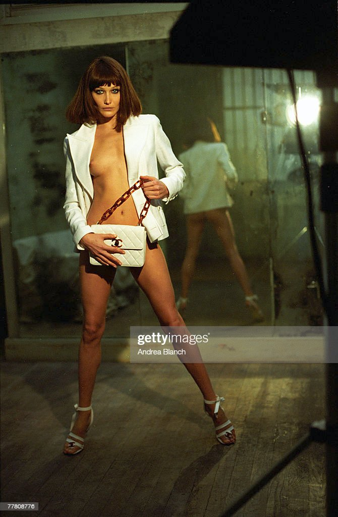Portrait of Italian fashion model Carla Bruni as she poses, dressed only in an open jacket, high heels, and a strategically placed handbag, as she poses for a photo shoot, 1995.
