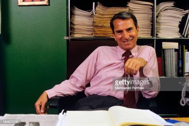 Portrait of Italian journalist Carlo Rossella at his desk 1990s