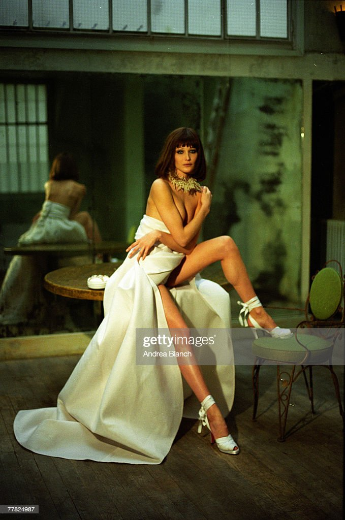 Portrait of Italian model <a gi-track='captionPersonalityLinkClicked' href=/galleries/search?phrase=Carla+Bruni&family=editorial&specificpeople=235729 ng-click='$event.stopPropagation()'>Carla Bruni</a> as she sits on a table, one high-heeled foot on a chair, and poses for a photo shoot, 1995.