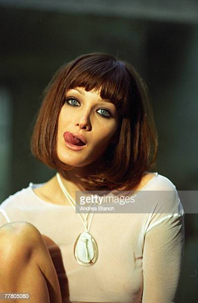Portrait of Italian model Carla Bruni in a transparent shirt as she licks her lips and poses for a photo shoot 1995