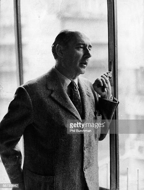 Portrait of Italian motion picture director Roberto Rossellini as he stands at a window in a tweed jacket and talks to someone out of frame Rome...