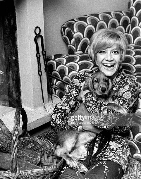 Portrait of Italian painter director and showgirl Gisella Pagano clasping in her arms a cocker spaniel and smiling Lierna 1970s
