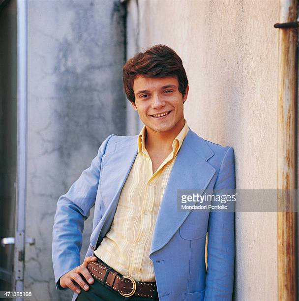 Portrait of Italian singer and theatre actor Massimo Ranieri leaning against a wall hand on hip in a photo shooting Italy 1971