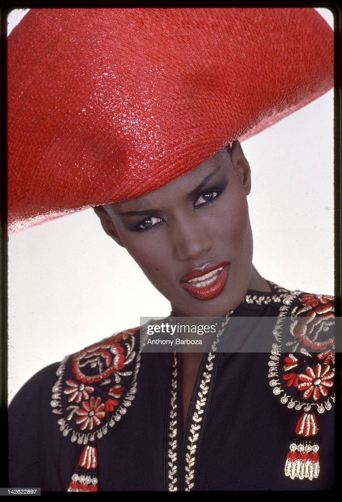 Portrait of Jamaican-born model, singer, and actress Grace Jones as she wears a bright red hat and multi-colored top, New York, New York, late twentieth century.