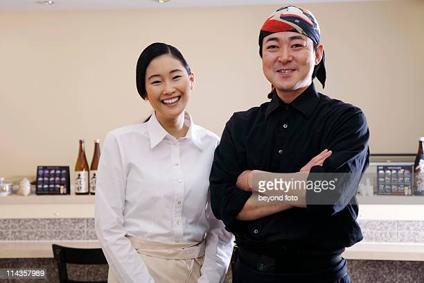 portrait of japanese waitress and chef in restaurant