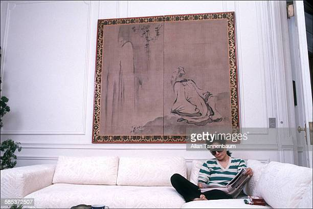 Portrait of Japaneseborn artist and musician Yoko Ono as she sits on a coach and reads in her home at the Dakota Apartments New York New York...
