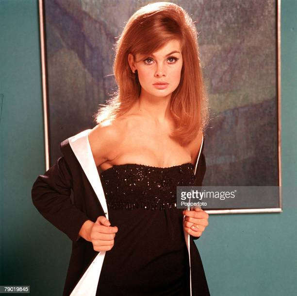 1965 A portrait of Jean Shrimpton wearing a black strapless evening dress whilst holding on a smart whitelined long black jacket with a serious...