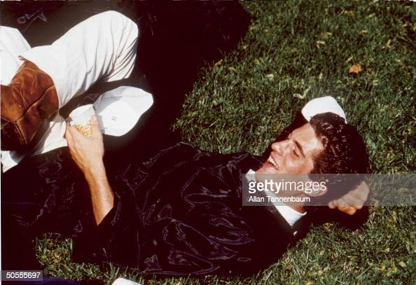 Portrait of John F Kennedy Jr as he lies on the the grass in his robe at his graduation from Brown University Rhode Island 1983