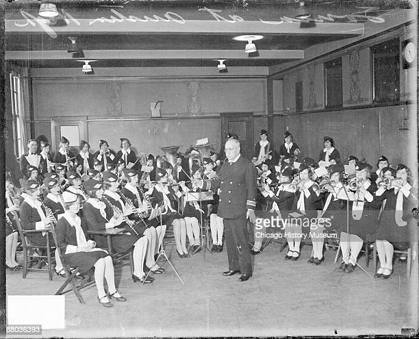 Portrait of John Philip Sousa American composer and bandmaster conducting an orchestra of young women wearing uniforms in a room at Austin High...