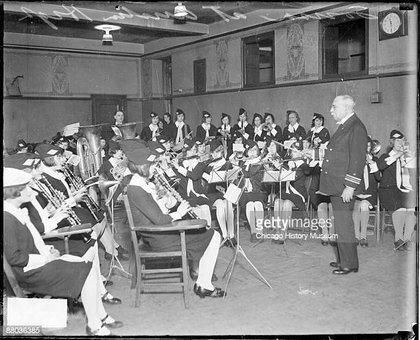 Portrait of John Philip Sousa American composer and bandmaster standing in profile and conducting an orchestra of young women wearing uniforms in a...