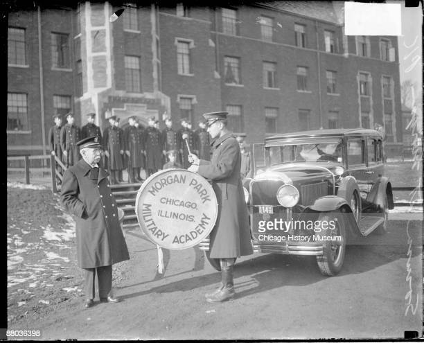 Portrait of John Philip Sousa American composer and bandmaster standing next to a young man wearing a military uniform and carrying a bass drum in...
