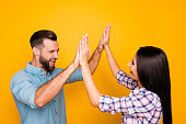 Portrait of joyful lucky couple giving high five with two hands enjoying victory in competition isolated on vivid yellow background