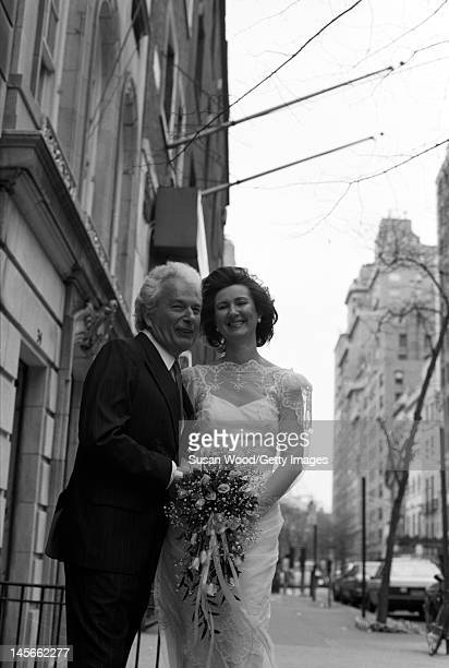 Portrait of just American author Joseph Heller and his bride Valerie Humphries on the sidewalk outside their wedding reception April 1987