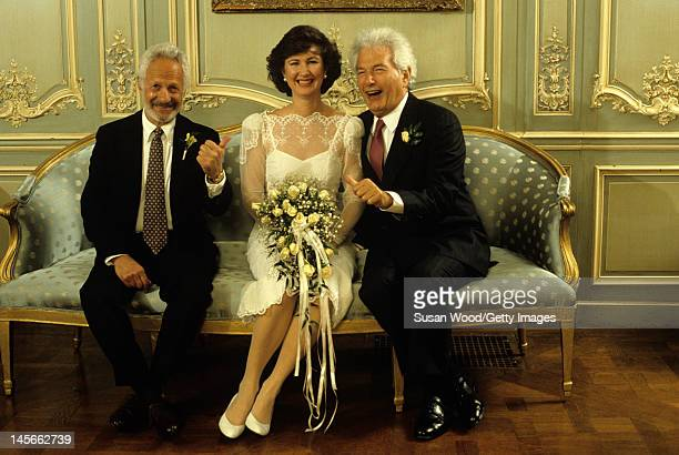 Portrait of justwed couple American author Joseph Heller and Valerie Humphries as they pose on their wedding day with Heller's friend artist Speed...