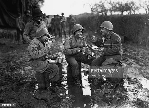 Portrait of Keystone War Correspondent and photographer Fred Ramage sharing a meal with two GI's in the muddy surrounding of the 9th Army Front...