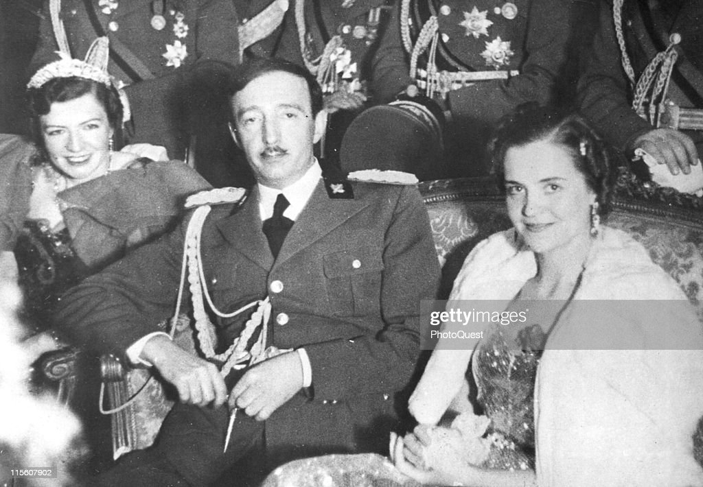 Portrait of King Zog of Albania (1895 – 1961) as he sits between two unidentified women at an unspecified event, late 1930s.