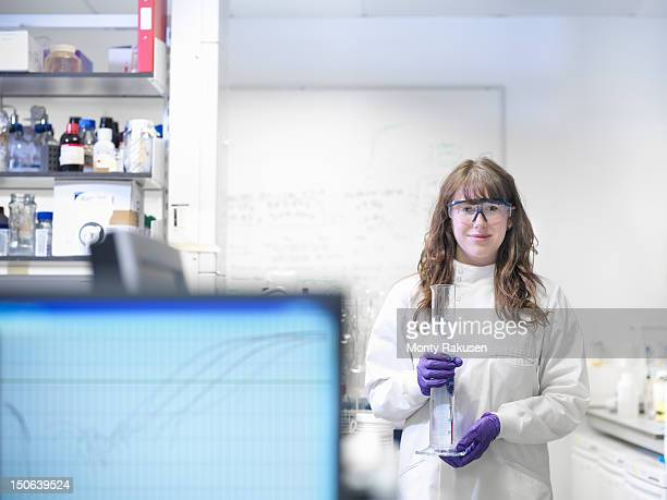 Portrait of laboratory technician holding measuring cylinder and working with genomic and protemcis