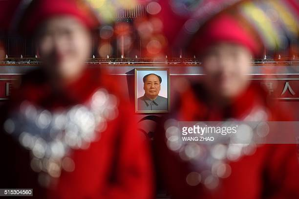 TOPSHOT A portrait of late communist leader Mao Zedong is seen behind two hostesses as they pose for a picture at the Tiananmen Square during the 3nd...