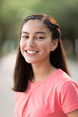 Portrait of a latin teen girl smiling at the camera in a vertical head and shoulders shot outdoors.