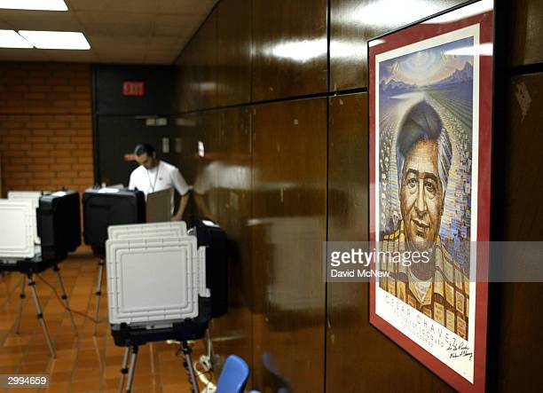 A portrait of Latino civil rights icon Cesar Chavez is on display as Rick Mata casts his ballot electronically on the first day of early voting in...