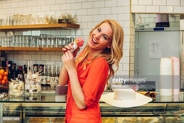 Portrait of laughing blond woman standing at counter in a ice cream parlour with ice cream cone