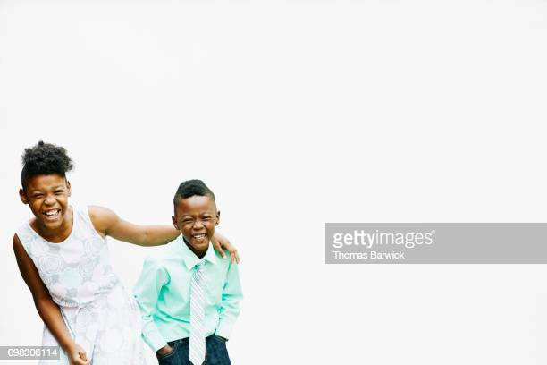 Portrait of laughing brother and sister in front of white background