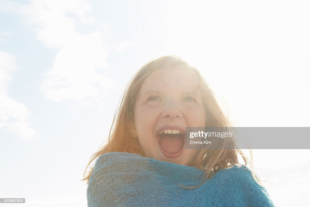 Portrait of laughing girl wrapped in towel at sunlit coast
