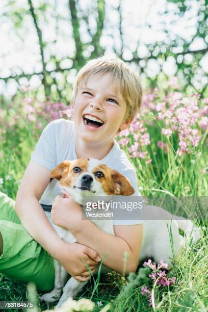 Portrait of laughing little boy sitting with his dog on meadow in the garden