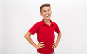Portrait of laughing little boy standing in front of white background looking at camera with hands on hips pose. Horizontal composition. Image taken with Nikon D800 and developed from Raw format. Stud