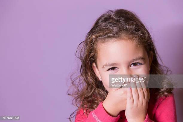 Portrait of laughing little girl covering mouth with her hands
