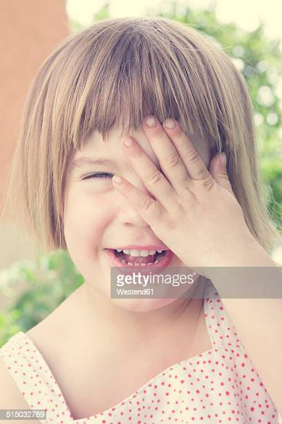 Portrait of laughing little girl covering one eye with her hand