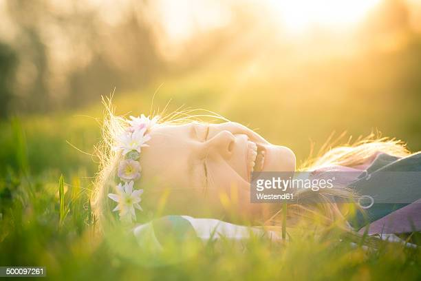 Portrait of laughing little girl lying on meadow wearing flowers