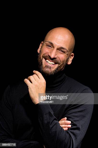 Portrait of laughing man wearing black turtleneck in front of black background
