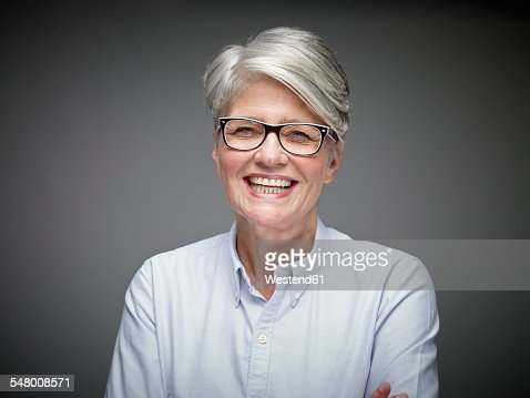 Portrait of laughing mature woman with grey hair in front of grey background