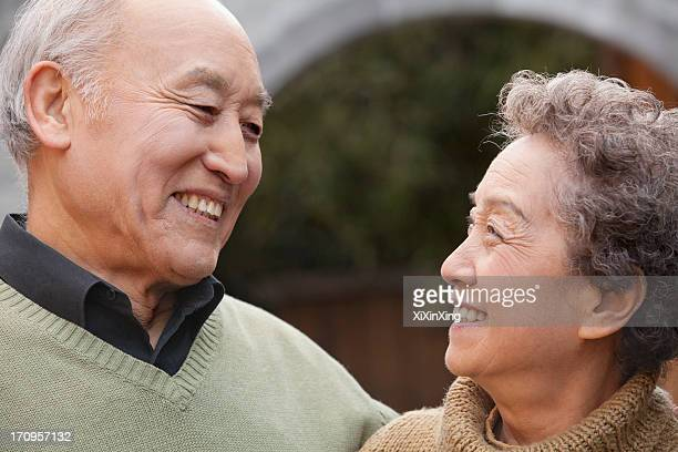 Portrait of laughing senior couple in front of round arch, Beijing