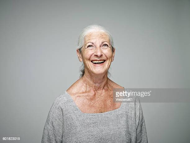 Portrait of laughing senior woman looking up in front of grey background