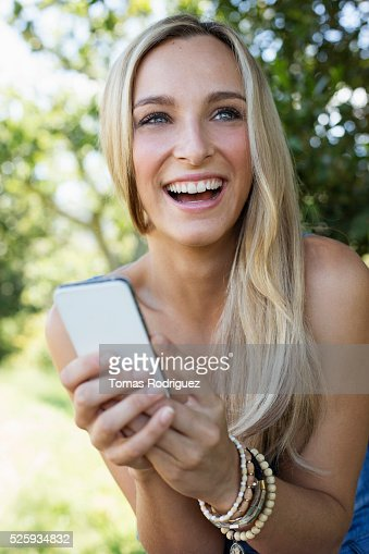Portrait of laughing woman holding cell phone : Stock Photo
