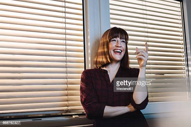 Portrait of laughing woman on window