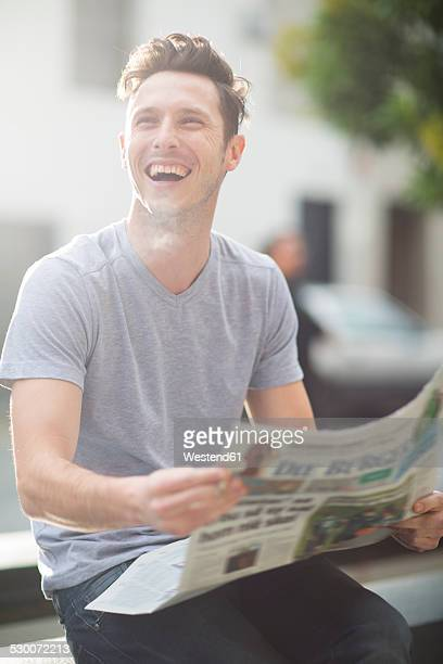 Portrait of laughing young man holding newspaper