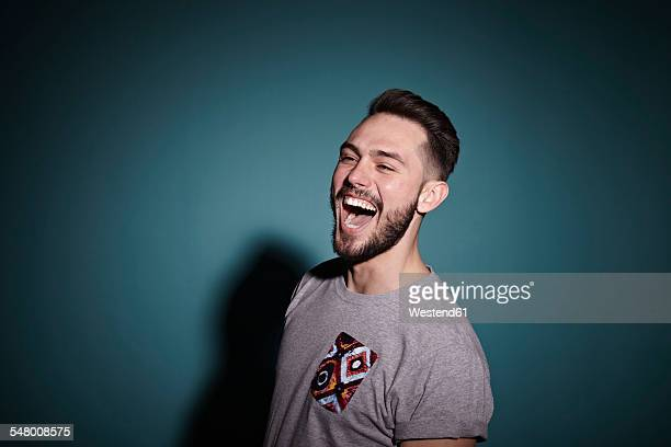 Portrait of laughing young man in front of blue background
