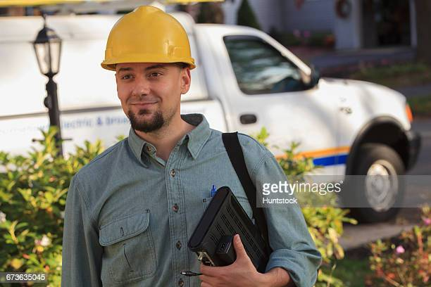 Portrait of lineman with cable box going to the house