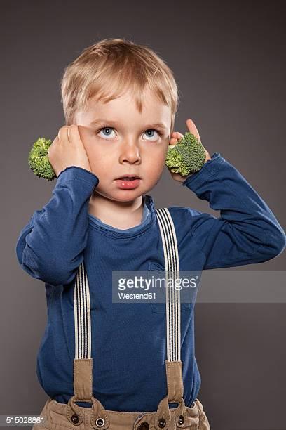 Portrait of little boy holding broccoli on his ears